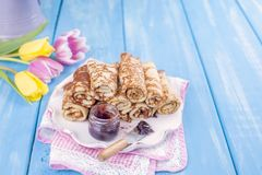 Homemade traditional pancakes with jam for spring carnival. Russian breakfast. Bright flowers of tulips. Blue background. Free. Space for text or a postcard stock photos