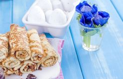 Homemade traditional pancakes with jam for spring carnival. Russian breakfast. Bright flowers of tulips. Blue background. Free. Space for text or a postcard royalty free stock photo