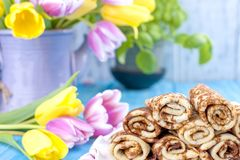 Homemade traditional pancakes with jam for spring carnival. Russian breakfast. Bright flowers of tulips. Blue background. Free. Space for text or a postcard stock photography