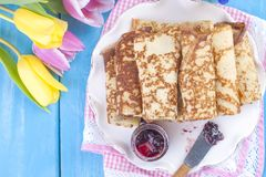 Homemade traditional pancakes with jam for spring carnival. Russian breakfast. Bright flowers of tulips. Blue background. Free. Space for text or a postcard stock photo