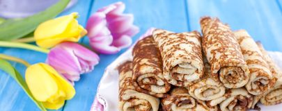 Homemade traditional pancakes with jam for spring carnival. Russian breakfast. Bright flowers of tulips. Blue background. Free. Space for text or a postcard royalty free stock images
