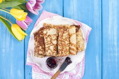 Homemade traditional pancakes with jam for spring carnival. Russian breakfast. Bright flowers of tulips. Blue background. Free. Space for text or a postcard royalty free stock photography