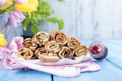 Homemade traditional pancakes with jam for spring carnival. Russian breakfast. Bright flowers of tulips. Blue background. Free. Space for text or a postcard stock images
