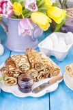 Homemade traditional pancakes with jam for spring carnival. Russian breakfast. Bright flowers of tulips. Blue background. Free. Space for text or a postcard stock image