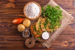 Homemade traditional potato pancakes Hanukkah celebration food with ingredients on vintage cutting board royalty free stock images