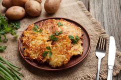 Homemade traditional potato pancakes or latke. Hanukkah celebration food in rustic clay dish on vintage wooden background. Natural light