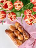 Homemade traditional Russian food, Pirozhki. And tulips on the table stock images