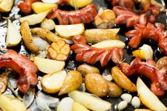 Homemade traditional sausages and potatoes in a black frying pan royalty free stock photography