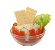 Homemade Tuna Salad Stuffed Tomato. Homemade tuna salad stuffed in a tomato with lettuce and crackers in a glass bowl on a white background Stock Images