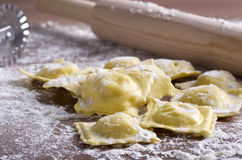 Homemade uncooked ravioli with a roller Royalty Free Stock Photo