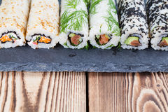 Homemade uramaki sushi rolls. On a slate board stock image