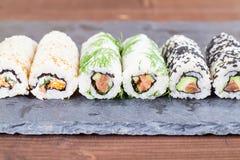 Homemade uramaki sushi rolls. On a slate board royalty free stock photos
