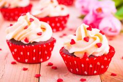 Homemade valentine cupcakes with red sugar hearts and pink tulips Royalty Free Stock Image