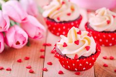 Homemade valentine cupcakes with red sugar hearts and pink tulips Stock Image