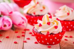 Homemade valentine cupcakes with red sugar hearts and pink tulips Stock Images