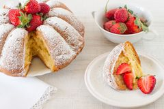 Spring dessert with bundt cake and fresh fruit. Homemade vanilla cake with strawberries close-up on the table royalty free stock image