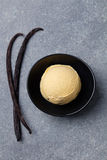 Homemade vanilla, caramel ice cream in black bowl with vanilla pods. Organic product Top view Copy space Royalty Free Stock Image