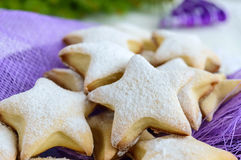 Homemade vanilla cookies in star-shaped decoration with powdered sugar on a purple napkin. Royalty Free Stock Photography