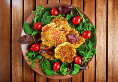 Homemade veg burgers from potatoes and lentils, served on a plate with tomatoes and green salad Royalty Free Stock Photo