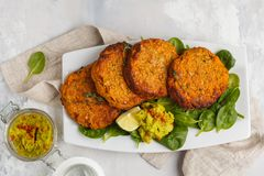 Homemade vegan baked sweet potato burgers in a white dish with g
