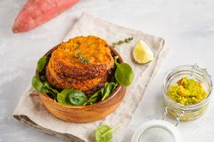 Homemade vegan baked sweet potato burgers in a wooden bowl, guacamole in a glass jar. Vegan Healthy Food Concept. Light