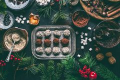 Homemade vegan chocolate truffle pralines for Christmas with dried fruits and nuts mix ingredients on dark background, top view,. Healthy sweets. Energy vegan stock image