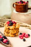 Homemade vegan crunchy oatmeal cookies with raspberry jam and date caramel on a grey wooden background.  stock image