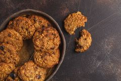 Homemade vegan oatmeal cookies with raisins, pecans and dates. H. Ealthy vegetarian dessert concept. Dark rusty background, copy space, top view stock images