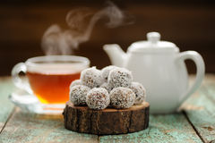 Homemade vegan sweets in coconut shavings served with steaming h. Ot black tea selective focus stock image