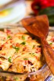 Homemade vegetable casserole with cheese. On a multicolor blurred background stock images