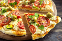Homemade vegetable pizza. With tomatoes, green olives, pepper, basil, oregano and cheese on wooden table with copy space Stock Photo
