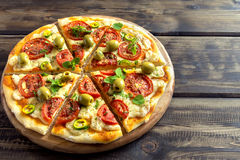 Homemade vegetable pizza. With tomatoes, green olives, pepper, basil, oregano and cheese on wooden table with copy space Stock Photography