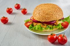 Homemade vegetarian burger with salad, onion rings, cheese, cherry tomatoes and mustard on the gray concrete background. With free copy space. Classic american Royalty Free Stock Photography
