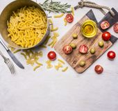 Homemade vegetarian pasta laid out in the bowl,  with herbs, oil, olives, cherry tomatoes on a wooden  board ,  place for t Stock Photos