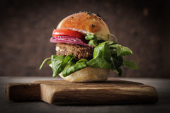 Homemade veggie burger in a bun sesame seeds of beer. Homemade veggie burger in a bun with sesame seeds of beer. delicious fast food for vegans. on a wooden stock photography