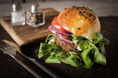 Homemade veggie burger in a bun sesame seeds of beer. Homemade veggie burger in a bun with sesame seeds of beer. delicious fast food for vegans. on a wooden royalty free stock image