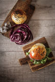 Homemade veggie burger in a bun sesame seeds of beer. Homemade veggie burger in a bun with sesame seeds of beer. delicious fast food for vegans. on a wooden stock photo