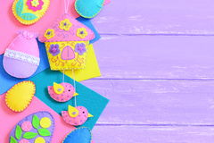 Homemade vibrant felt Easter crafts on lilac wooden background with empty copy space for text Royalty Free Stock Images