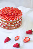Homemade Victoria summer dessert layer cake with whipped cream topping, decorated with strawberries. Close up on the Royalty Free Stock Image