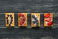 Homemade waffles with cream and berries on a black wooden rustic background. He lay flat. stock images