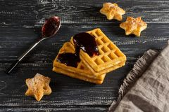 Homemade waffles with jam on an old wooden table. Wafers with linen napkin and spoon in jam. Homemade waffles with jam on an old wooden table. Wafers with linen Royalty Free Stock Photos