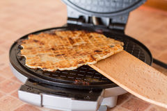 Homemade waffles in a waffle iron with wood spatula. Stock Photography