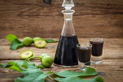Homemade wallnut liquer on rustic wooden background. Bottle and two glasses with walnut liquor. Homemade wallnut liquer on rustic wooden background royalty free stock photo
