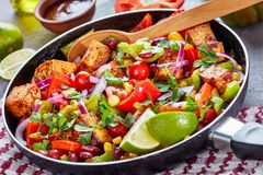 Homemade warm black bean and corn salsa salad. With tomatoes and peppers, fried tofu cheese, lime juice and olive oil dressing in a cast-iron skillet on a stock images