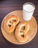 Homemade warm soft pretzels and glass of milk. On a table Royalty Free Stock Images