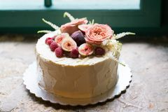 Homemade wedding cake decorated with flowers and fruits. Near the window Stock Image