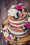 Homemade wedding naked cake. Decorated with flowers on wooden cut stand, shot from top Royalty Free Stock Photo
