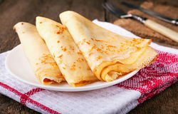 Homemade wheat crepes or pancakes with strawberry jam or marmalade stacked on a plate on a wooden rustic table royalty free stock photography