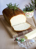 Homemade white bread. Delicious homemade white bread loaf on wood cutting board with butter and rosemary, Christmas bread set up on fabric table cloth for Royalty Free Stock Images