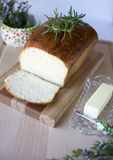 Homemade white bread. Delicious homemade white bread loaf on wood cutting board with butter and rosemary, Christmas set up for holiday dinner Royalty Free Stock Photography